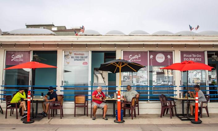 People sit outside a restaurant and bar in Hermosa Beach, Los Angeles, California, 14 July 2020.