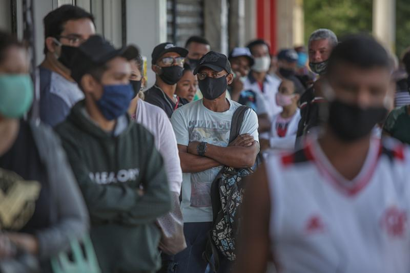 RIO DE JANEIRO, BRAZIL - MAY 04: People using protective masks wait in line outside a Caixa Economica Federal bank branch in Vila Kosmos neighborhood to receive urgent government benefit amidst the coronavirus (COVID - 19) pandemic on monday, May 04, 2020 in Rio de Janeiro, Brazil. (Photo by Andre Coelho/Getty Images)