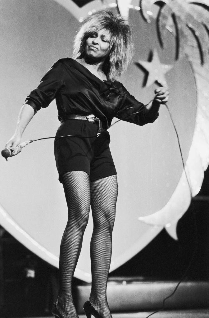 <p>Tina Turner took black, high waisted shorts and turned them up a notch with a belt and fishnet stockings. </p>