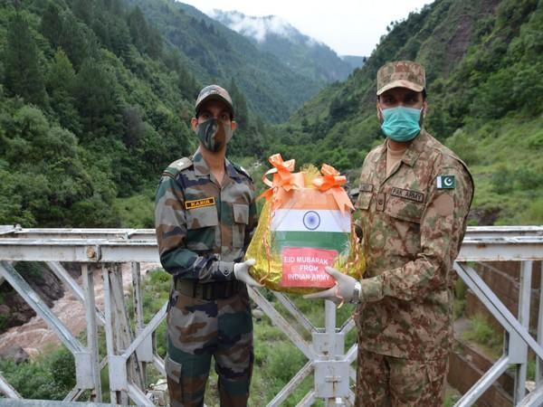 Troops of BSF and Pakistan Rangers exchangimng sweets on the occasion of Eid-Ul-Adha, at the Indo-Pak Border in Jammu.
