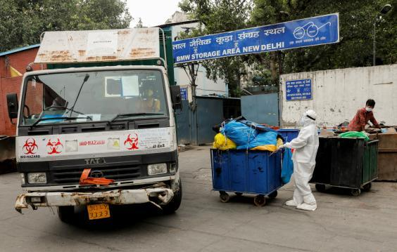 A medical staff member pushes a trolley containing medical waste bags to a storage area (Reuters)