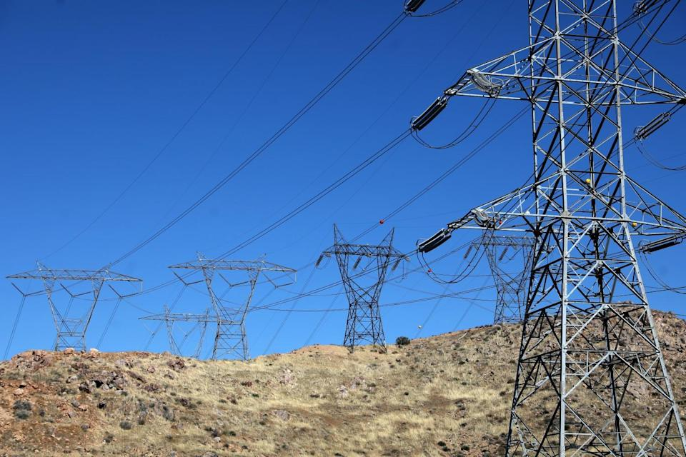 Electric transmission lines are seen on a hill.