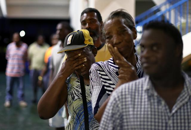 <p>Barbuda resident Diamn Beazer (third in line) waits for food at a shelter in the Sir Vivian Richards Cricket Stadium on Sept. 20, 2017 in North Sound, Antigua and Barbuda. Refugees from the island of Barbuda are been housed after the government ordered a mandatory evacuation in response to Hurricane Irma's devastation of the Caribbean Island. (Photo: Jose Jimenez/Getty Images) </p>