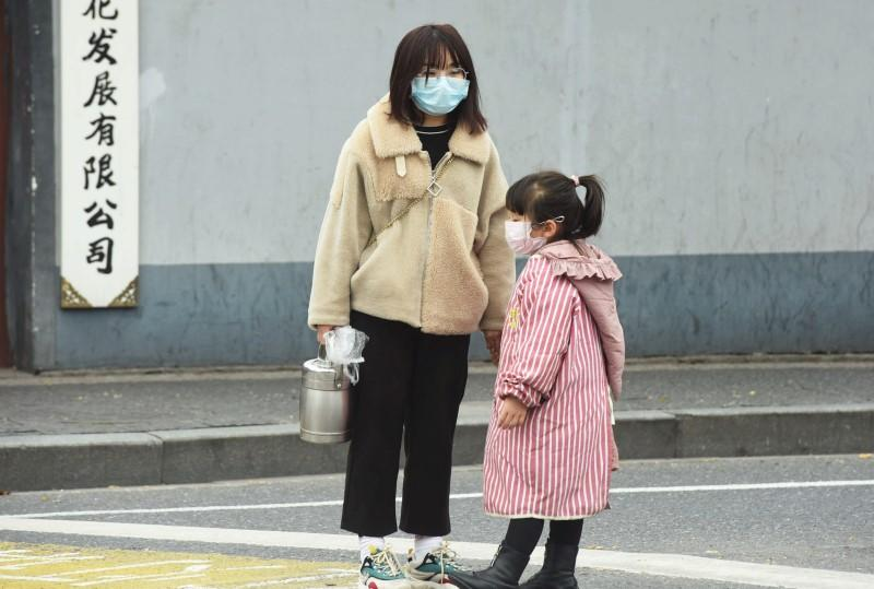 Woman and a child wearing masks stand on a street in Hangzhou