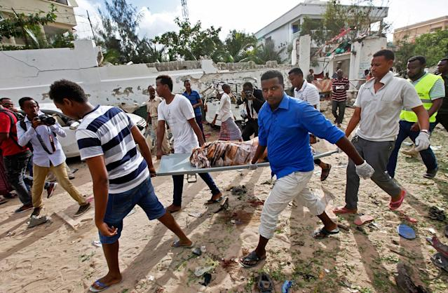 <p>Somali men carry away the body of a civilian who was killed in a militant attack on a restaurant in Mogadishu, Somalia Thursday, June 15, 2017. (Photo: Farah Abdi Warsameh/AP) </p>