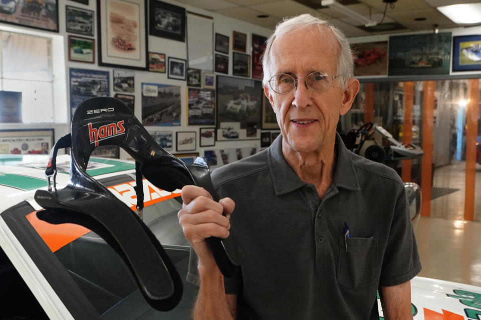 Jim Downing poses with the HANS (Head And Neck Support) device he co-invented with his brother-in-law, Wednesday, Sept. 1, 2021, at his race shop in Atlanta. The device keeps a driver's head from violently snapping forward in an accident and has been credited with saving numerous lives in its two decades of use. (AP Photo/John Bazemore)