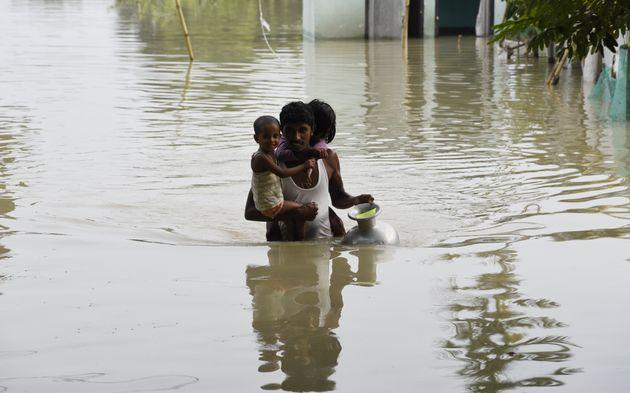 A man carries his children to a safer place in a flood-affected village of Kamrup district of Assam, India, on July 14, 2020.