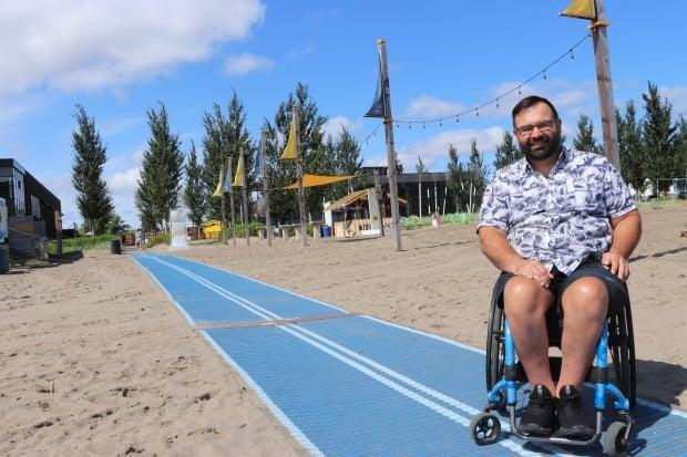 Since he started using a wheelchair 26 years ago, Maxime Boily  has struggled to cross the sand in his wheelchair. Now, with a new mat at the Baie de Beauport, Boily is able to get to the water with ease.  (Franca Mignacca/CBC  - image credit)