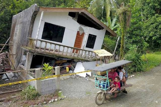 A motorist drives past a destroyed house after a large earthquake that hit Surigao City, Philippines (AFP Photo/ERWIN MASCARINAS)