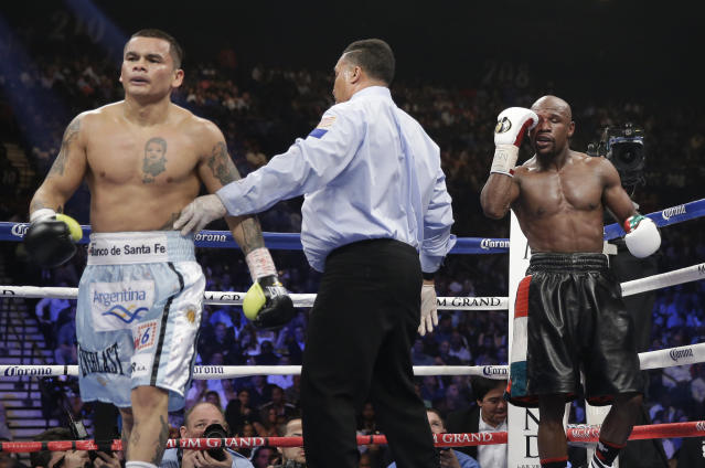 Marcos Maidana, left, is sent to his corner by referee Tony Weeks, center, after accidentally head butting Floyd Mayweather Jr. in their WBC-WBA welterweight title boxing fight Saturday, May 3, 2014, in Las Vegas. (AP Photo/Isaac Brekken)