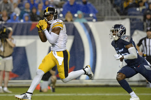 FILE - In this Aug. 25, 2019, file photo, Pittsburgh Steelers wide receiver JuJu Smith-Schuster catches a 17-yard touchdown pass ahead of Tennessee Titans cornerback LeShaun Sims (36) in the first half of a preseason NFL football game in Nashville, Tenn. Smith-Schuster is looking for a big bounce-back this season. (AP Photo/Mark Zaleski, File)
