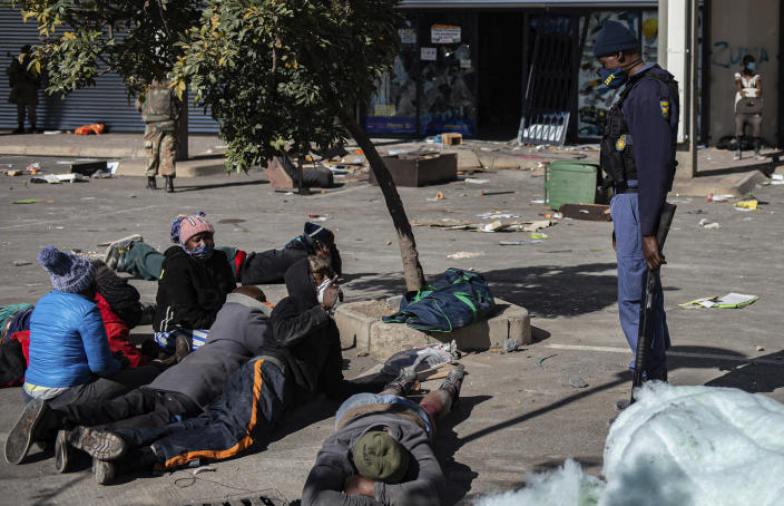 A policeman watches over arrested looting suspects at a shopping centre, in Soweto near Johannesburg, Tuesday July 13, 2021 as ongoing looting and violence continues. South Africa's rioting continued Tuesday with the death toll rising to 32 as police and the military struggle to quell the violence in Gauteng and KwaZulu-Natal provinces. The violence started in various parts of KwaZulu-Natal last week when Zuma began serving a 15-month sentence for contempt of court. (AP Photo/Ali Greeff)