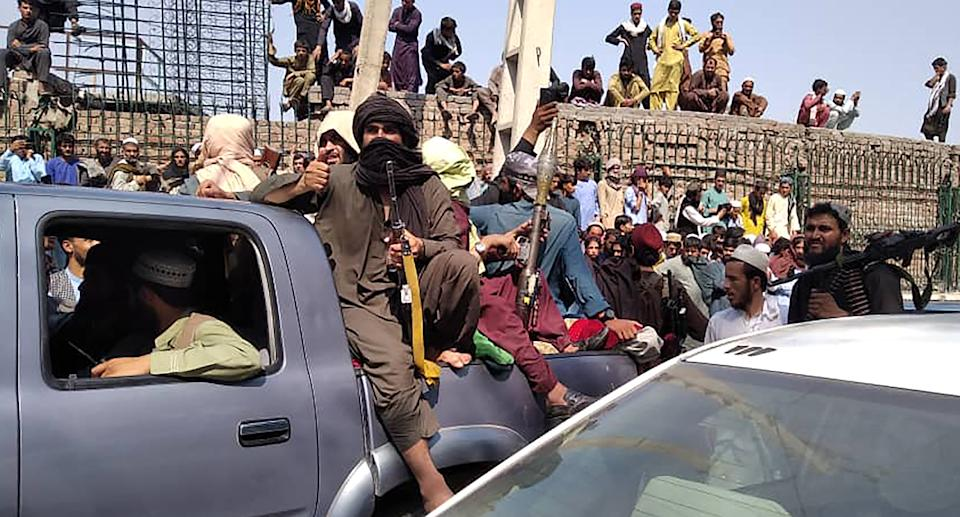 Taliban fighters sit on a vehicle along the street in Jalalabad province on August 15, 2021. (-/AFP via Getty Images)
