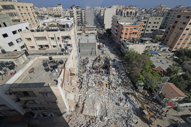 Palestinian rescue teams search for survivors under the rubble of a destroyed building in Gaza City's Rimal residential district on May 16
