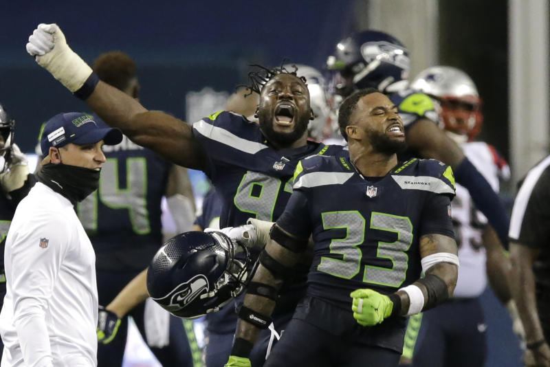 Seattle Seahawks' Jamal Adams (33) and L.J. Collier, left, celebrate after the Seahawks beat the New England Patriots 35-30. (AP Photo/John Froschauer)