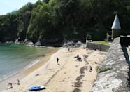 <p>Light wind, postcard perfect scenery and sundrenched sands make this sweet seaside spot the perfect picnic destination in Cornwall. Out in the sheltered bay a wooden platform anchored beneath the cliffs makes a great spot for swimmers. The nearby fishing port boasts plenty of shops and colourful cafes for pasties and ice cream. </p><p><strong>Don't Miss</strong>: Cool off with ice cream or a milkshake from the cleverly-named sweet shop, Game of Cones.</p>