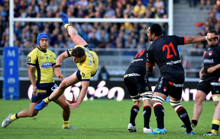 Clermont's Damian Penaud (L) loses balance as he attempts to catch the ball during their French Top 14 rugby union match against Lyon on April 29, 2017