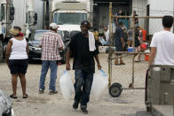 In the aftermath of Hurricane Ida, residence pick up food and ice at a distribution center Wednesday, Sept. 1, 2021, in New Orleans, La. (AP Photo/Eric Gay)