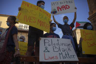 Protesters hold signs during a demonstration against the Israeli police after border police officers shot and killed Iyad al-Halak, an unarmed autistic Palestinian man, in the mixed Arab Jewish city of Jaffa, near Tel Aviv, Israel, after saying they suspected he was carrying a weapon, Sunday, May 31, 2020. Protesters gathered to protest the killing of al-Halak in Jerusalem and the killing of George Floyd in Minneapolis last week. (AP Photo/Oded Balilty)