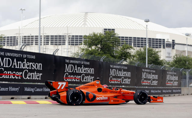 Simon Pagenaud, of France, drives near the Astrodome during a practice session for the IndyCar Grand Prix of Houston auto race Friday, June 27, 2014, in Houston. (AP Photo/David J. Phillip)