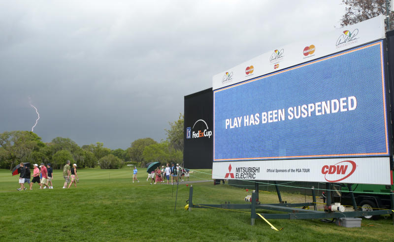 Lightning strikes in the distance as spectators leave the course after play was suspended due to an approaching severe thunderstorm during the final round of the Arnold Palmer Invitational golf tournament in Orlando, Fla., Sunday March 24, 2013.(AP Photo/Phelan M. Ebenhack)