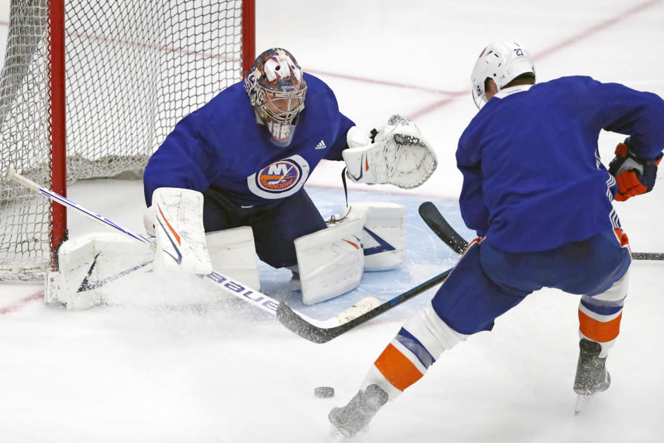 New York Islanders goaltender Semyon Varlamov, left, prepares for a shot by Islanders left wing and captain Anders Lee during an NHL hockey team practice, Monday, July 13, 2020, at the team's practice facility in East Meadow, N.Y. (AP Photo/Kathy Willens)