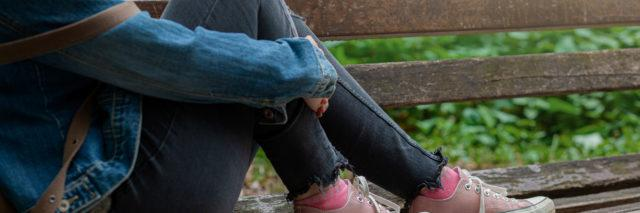 blonde woman in jeans sitting on park bench