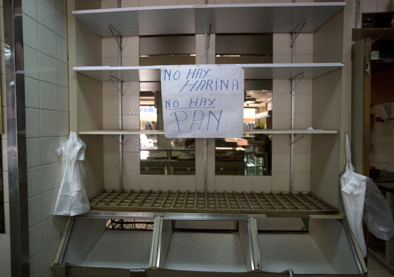 """FILE - In this March 20, 2017 file photo, a handwritten message that reads in Spanish: """"No flour. No bread"""", is taped to the edge of an empty shelf at a privately owned bakery in Caracas, Venezuela. Russia is offering to alleviate Venezuela's food shortage crisis. The Venezuelan Foreign Ministry announced Friday, May 19, 2017, that Russian President Vladimir Putin had promised to start delivering several thousand tons of wheat after speaking on the phone with President Nicolas Maduro. (AP Photo/Fernando Llano, File)"""