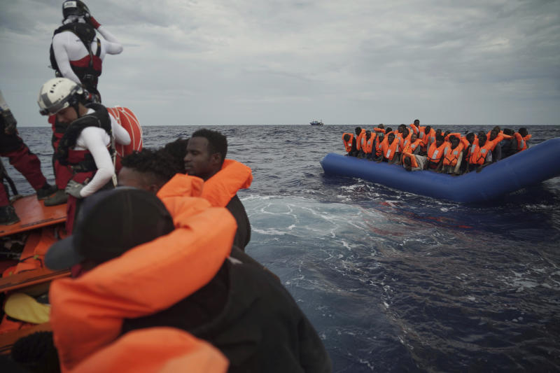 Migrants on a blue rubber boat wait to be rescued some 14 nautical miles from the coast of Libya in Mediterranean Sea, Sunday, Sept. 8, 2019. Humanitarian groups SOS Mediterranee and Doctors Without Borders have successfully rescued 50 migrants and brought them aboard the Ocean Viking. (AP Photo/Renata Brito)