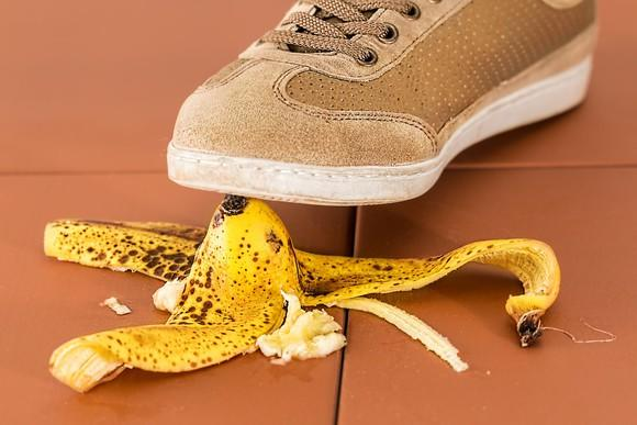 A closeup of a sneaker about to step on a banana peel