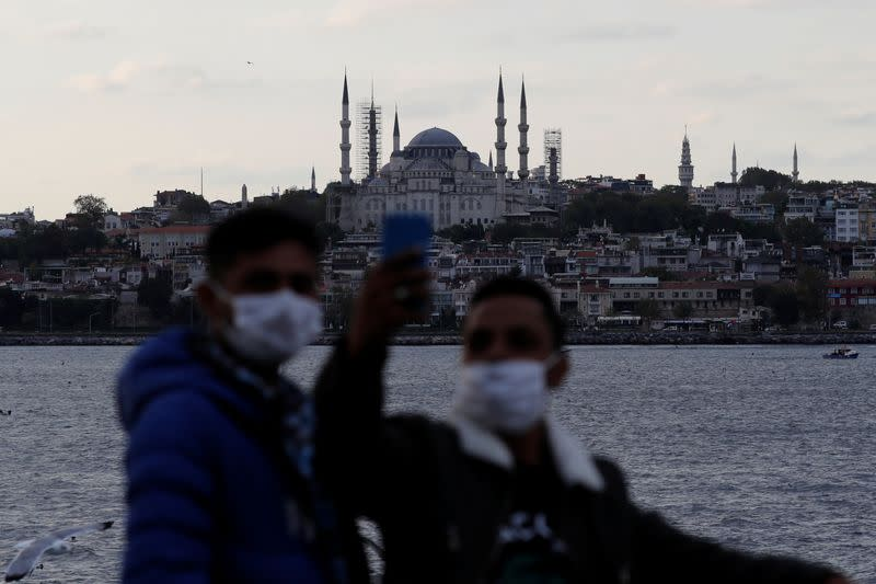 Men wearing protective face masks pose for a selfie with the Blue Mosque as they travel in a ferry in Istanbul