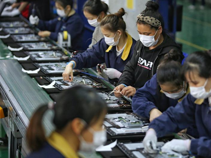 Employees work on a production line manufacturing display monitors at a TPV factory in Wuhan on April 7, 2020.