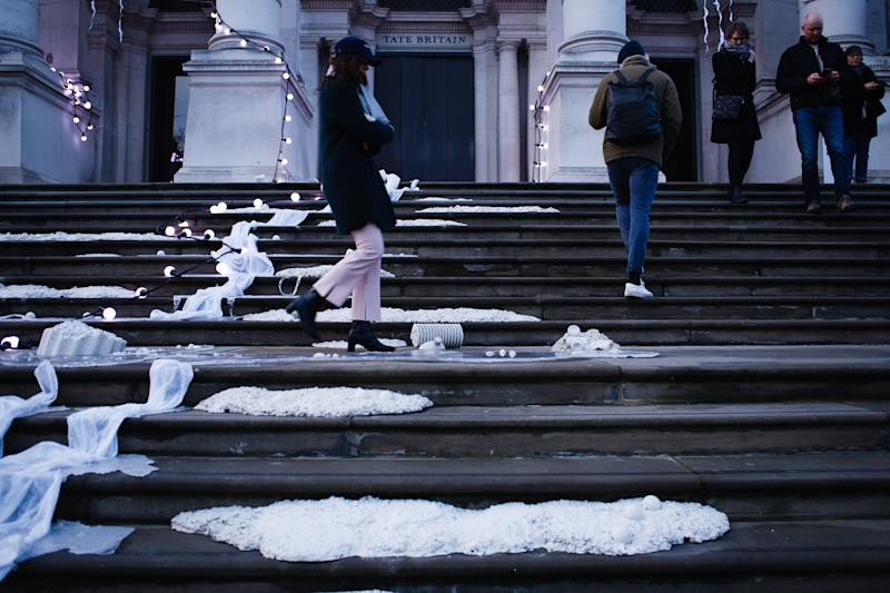 People walk across the light-and-sound installation 'The Depth Of Darkness The Return Of The Light', by artist Anne Hardy, on the steps of the Tate Britain art gallery in London, England, on November 30, 2019. Hardy's piece, unveiled today as the gallery's 2019 Winter Commission, is intended to make the building resemble a 'marooned temple'. A thundery soundtrack accompanies the physical objects fixed to the steps and masonry of the front of the gallery. The installation will remain in place until January 26 next year. (Photo by ) | David Cliff—NurPhoto/Getty Images