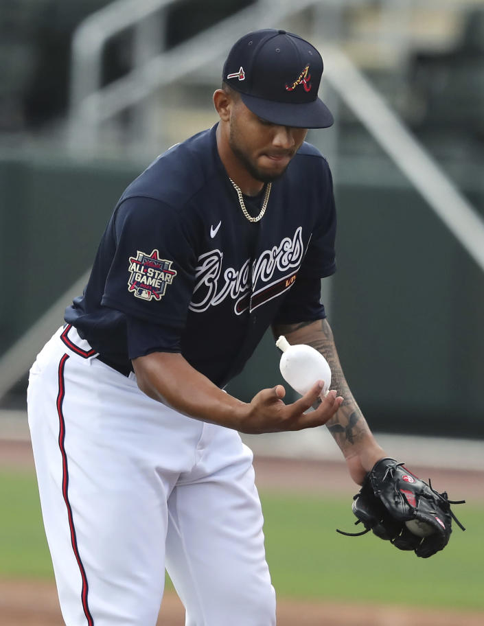 Atlanta Braves pitcher Huascar Ynoa powders his throwing hand with a rosin bag while throwing live batting practice during baseball spring training, Wednesday, Feb. 24, 2021, in North Port, Fla. (Curtis Compton/Atlanta Journal-Constitution via AP)