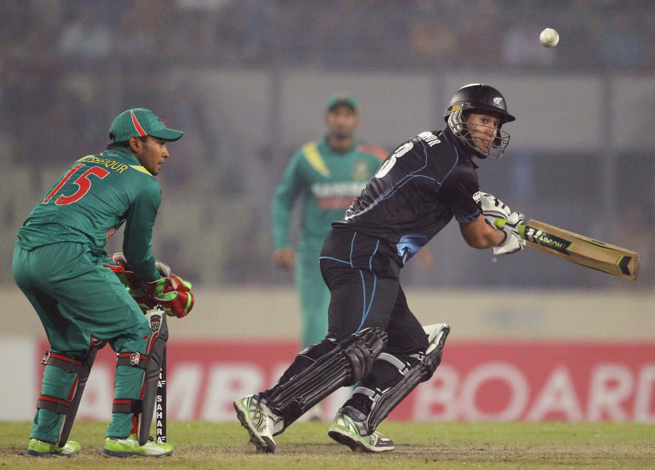 New Zealand's Ross Taylor plays a shot as Bangladesh's Mushfiqur Rahim (L) watches during their second one-day international (ODI) cricket match in Dhaka October 31, 2013. REUTERS/Andrew Biraj (BANGLADESH - Tags: SPORT CRICKET)