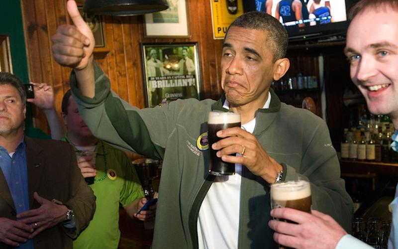 Obama gives a thumbs-up as he celebrates St. Patrick's Day with a pint of Guinness during a stop at the Dubliner Irish pub in Washington - Credit: Reuters