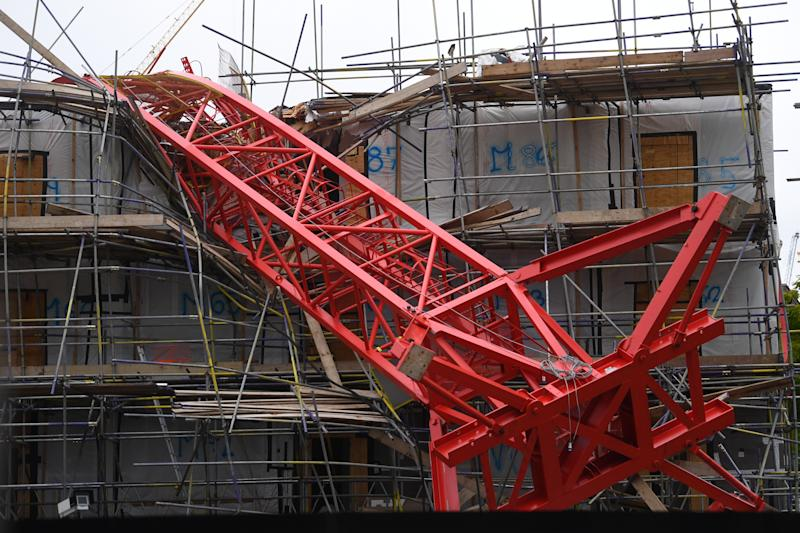 Emergency personnel at the scene in Bow, east London, where a 20-metre crane has collapsed on to a house leaving people trapped inside.