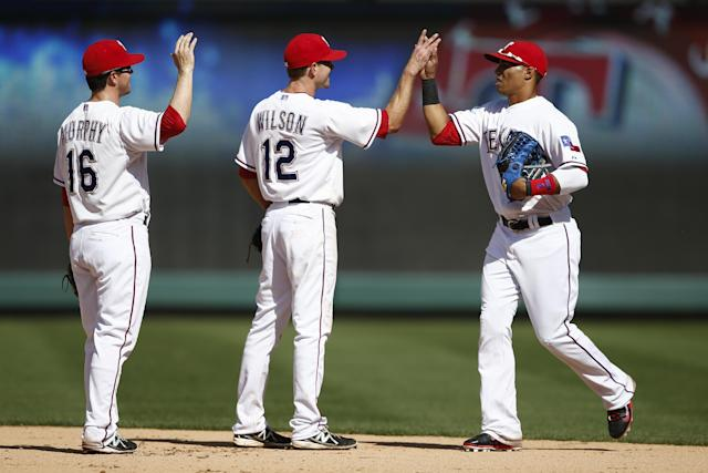 Texas Rangers' Donnie Murphy and Josh Wilson line up to celebrate with Leonys Martin following a baseball game against the Houston Astros, Sunday, April 13, 2014, in Arlington, Texas. The Rangers won 1-0. (AP Photo/Jim Cowsert)