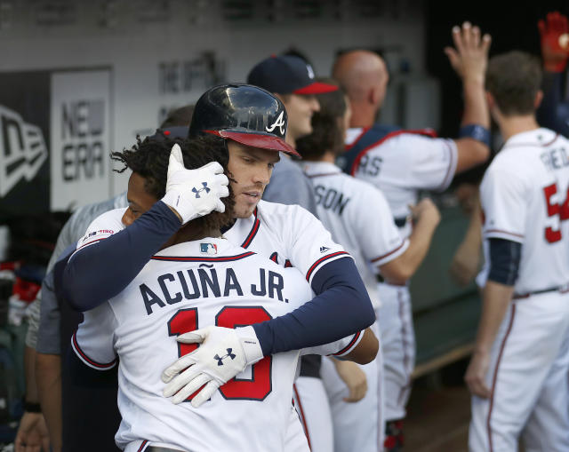 Atlanta Braves' Freddie Freeman (5) embraces teammate Ronald Acuna Jr., (13) after hitting a two-run home run in the first inning of a baseball game against the New York Mets Wednesday, June 19, 2019, in Atlanta. (AP Photo/John Bazemore)