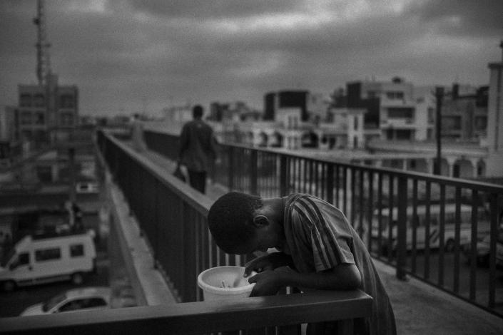 <p>A talibe begs on a bridge in the Diamaguene area, Senegal, May 18, 2015. Children are forced to beg for an average of eight hours a day; many spend their days almost without eating and end up sleeping on the street due to accumulated fatigue. (Photograph by Mario Cruz) </p>