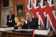 UK chief trade negotiator David Frost looks on as Britain's Prime Minister Boris Johnson signs the EU-UK Trade and Cooperation Agreement at 10 Downing Street, London Wednesday Dec. 30, 2020. The U.K. left the EU almost a year ago, but remained within the bloc's economic embrace during a transition period that ends at midnight Brussels time —- 11 p.m. in London — on Thursday. European Commission President Ursula von der Leyen and European Council President Charles Michel signed the agreement during a brief ceremony in Brussels on Wednesday morning then the documents were flown by Royal Air Force plane to London for Johnson to add his signature. (Leon Neal/Pool via AP)
