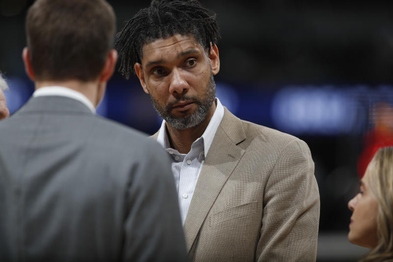 San Antonio Spurs assistant coach Tim Duncan listens during a coaches' huddle in the first half of an NBA basketball game agaisnt the Denver Nuggets Monday, Feb. 10, 2020, in Denver. (AP Photo/David Zalubowski)