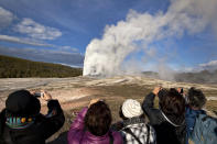 FILE - In this May 21, 2011 file photo, tourists photograph Old Faithful erupting on schedule late in the afternoon in Yellowstone National Park, Wyo. On Tuesday, March 24, 2020 the National Park Service announced that Yellowstone and Grand Teton National Parks would be closed until further notice, and no visitor access will be permitted to either park..(AP Photo/Julie Jacobson, File)