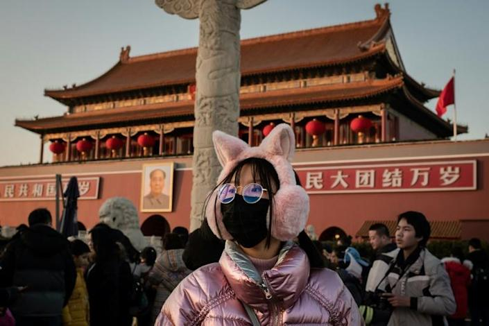 A woman wears a protective mask at Tiananmen Gate in Beijing. China is halting public transport and closing highway toll stations in two more cities in Hubei province, the epicentre of a deadly virus outbreak. (AFP Photo/NICOLAS ASFOURI)
