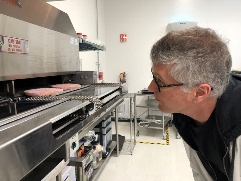 FILE PHOTO: Impossible Foods Chief Executive Pat Brown poses in front of a flame broiler cooking its plant-based patties at a facility in Redwood City