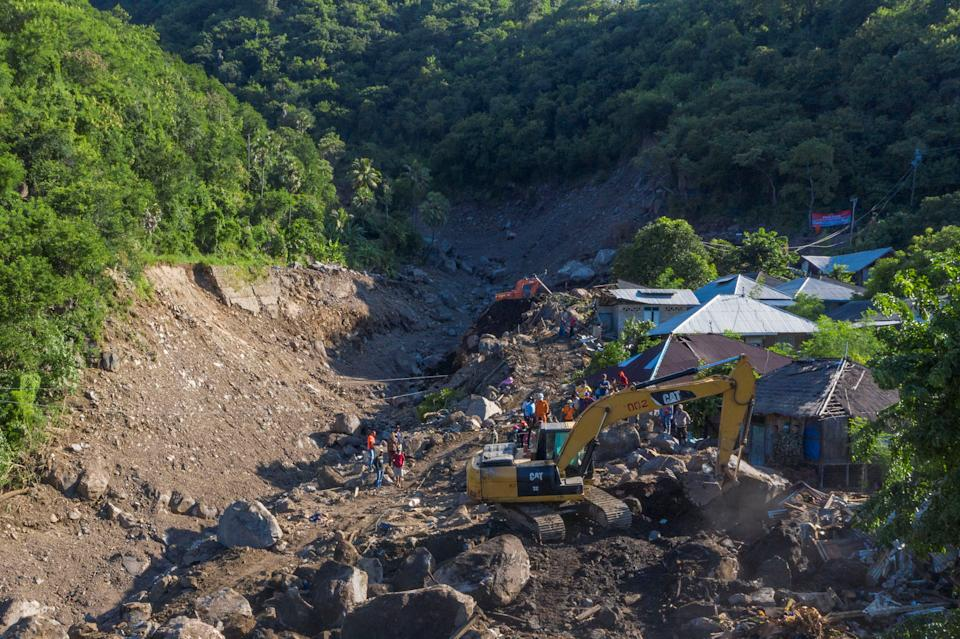 An aerial picture shows an excavator search for a body at an area affected by landslides triggered by tropical cyclone Seroja in Lembata, East Nusa Tenggara province, Indonesia.
