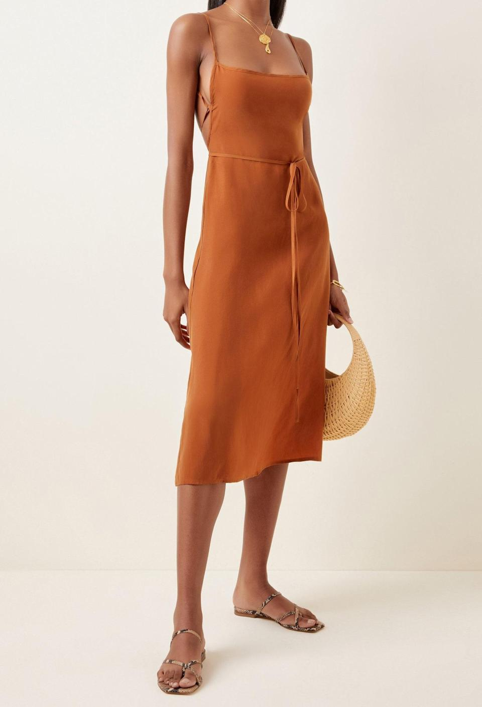 """Go from the reception to the beach in this open-backed washed cupro dress from resort brand Anemos. $345, Moda Operandi. <a href=""""https://www.modaoperandi.com/women/p/anemone/k-m-tie-midi-dress-in-rust-sandwashed-cupro/459536"""" rel=""""nofollow noopener"""" target=""""_blank"""" data-ylk=""""slk:Get it now!"""" class=""""link rapid-noclick-resp"""">Get it now!</a>"""