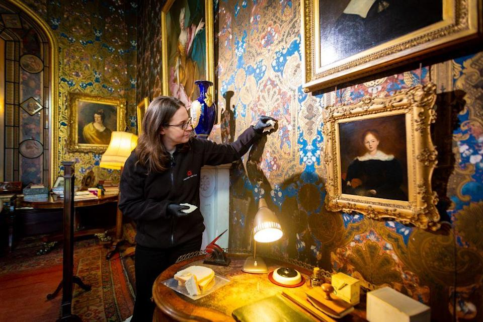 A conservator uses bread to wipe down wallpaper at Brodsworth Hall in Yorkshire as part of its annual spring clean (English Heritage/PA)