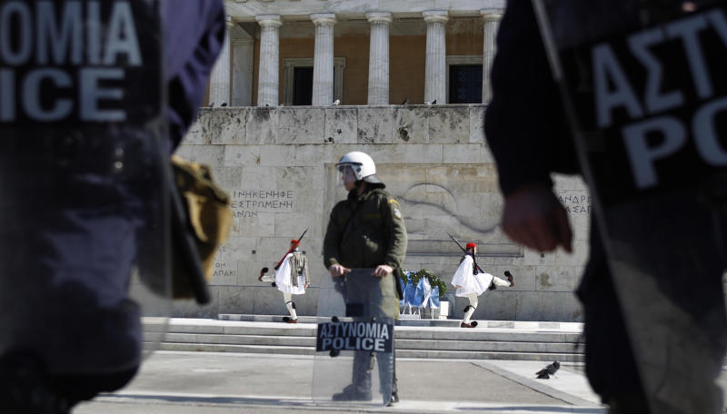 Greek presidential guard, known as Evzones, takes part in a changing of the guard ceremony at the Tomb of the Unknown Soldier, in front of a riot police who secure the Greek parliament, in central Athens as few hundred protesters gathered to protest against austerity measures during an anti-government rally on Sunday, Feb. 19, 2012.(AP Photo/Petros Giannakouris)