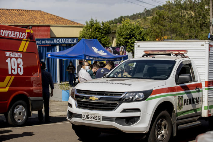 Relatives stand amid emergency vehicles, outside the Aquarela preschool in Saudades, in the southern state of Santa Catarina, Brazil, Tuesday, May 4, 2021. According to the police an 18-year-old teenager entered the day care center with a knife and stabbed and killed three children and a teacher. (AP Photo/Liamara Polli)